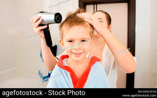 Portrait of mother and little boy drying hair with hairdryer after having bath. Concept of child hygiene and health care at home