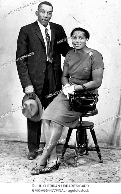 Portrait of African-American couple wearing hat, suit and formal dress, in photographic studio, 1930