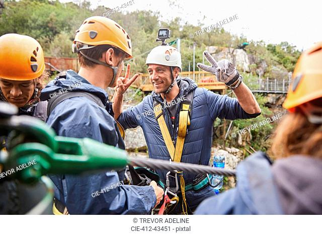 Enthusiastic man preparing to zip line, gesturing peace sign