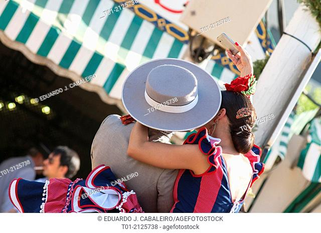 couple kissing and getting a photo with the phone in the April Fair of Seville
