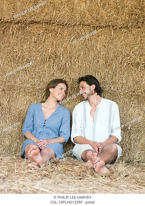 Man and woman sitting against hay bale