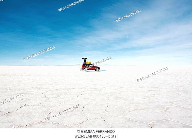 Bolivia, Potosi, man standing on his 4x4 in the Uyuni Salt Flats