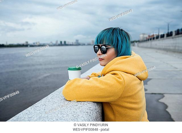 Young woman with dyed blue hair leaning on a wall looking at distance