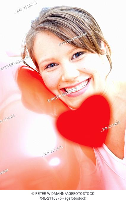 Young woman with pink hearts, laughing (model-released)
