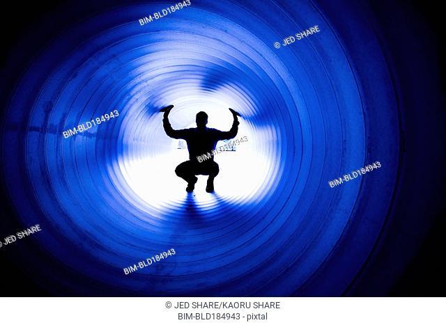 Silhouette of Caucasian man in tunnel