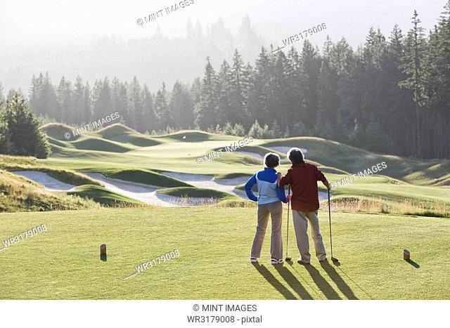 Senior golfing couple surveying the next tee shot toward the green