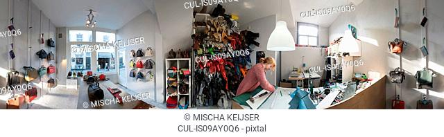 Wide angle view of woman in workshop in leather bag shop