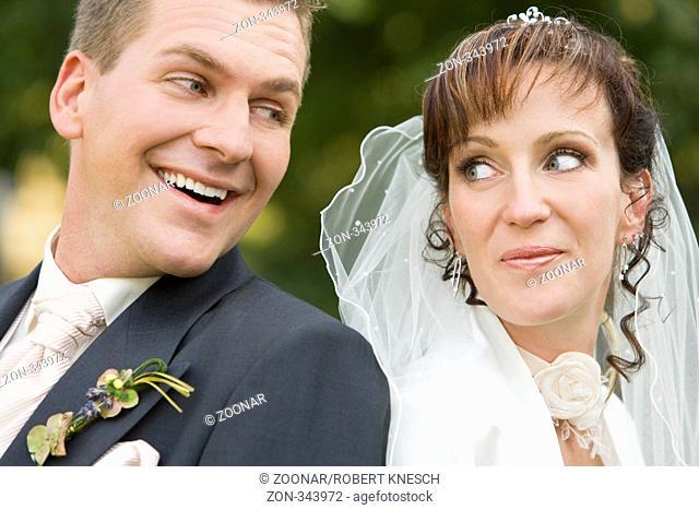 Junges Brautpaar lehnt Rücken an Rücken und schaut sich an
