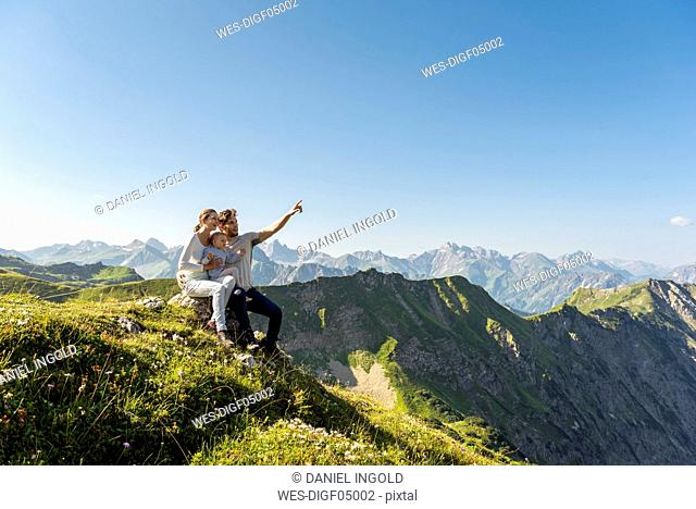 Germany, Bavaria, Oberstdorf, family with little daughter on a hike in the mountains having a break looking at view