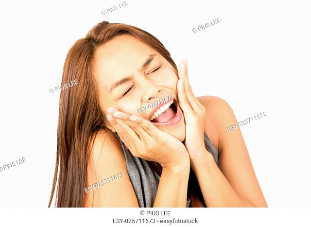 High angle portrait of panicked Asian girl in casual sleeveless clothes, head in hands, cupping face screaming with eyes closed looking up reacting to terrible...