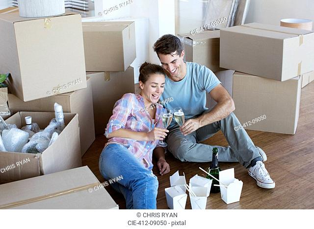 Couple enjoying champagne and Chinese take out food in new house