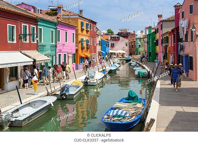 Many tourists walking on a Burano streets along the canal, passing trough the typical colorful houses, Burano, Venice, Veneto, Italy