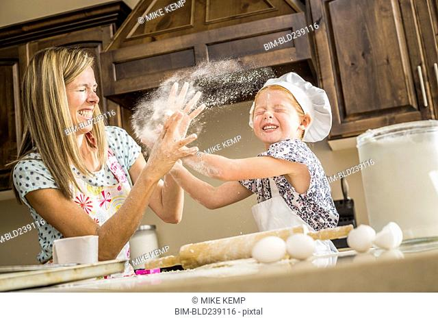 Caucasian mother and daughter having food fight with flour