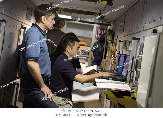 Russian cosmonaut Yuri Malenchenko (left) and Japan Aerospace Exploration Agency (JAXA) astronaut Akihiko Hoshide, both Expedition 3233 flight engineers; and...