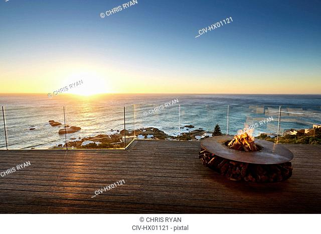 Fire pit on luxury patio with sunset ocean view