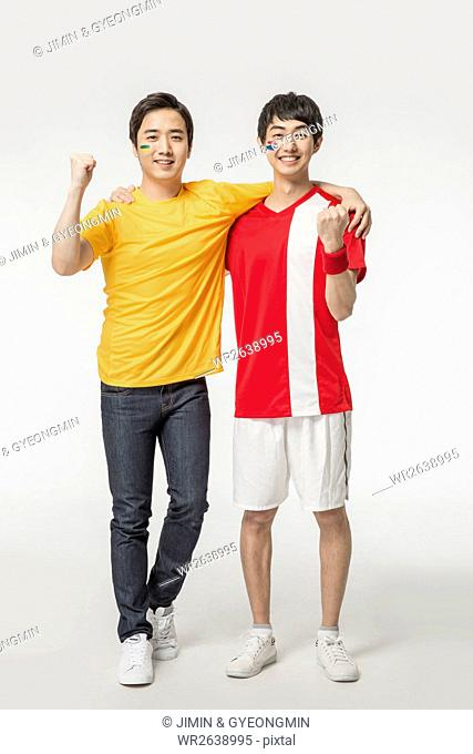 Two young smiling men with arms on each other's shoulders cheering