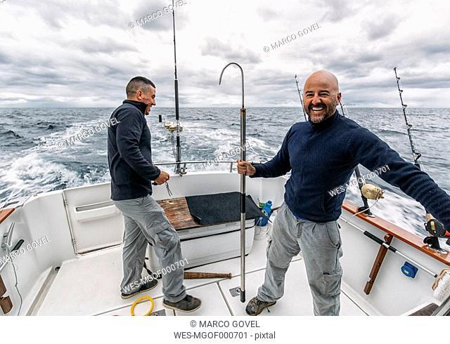 Spain, Asturias, Fishermen on fishing boat on Cantabrian Sea