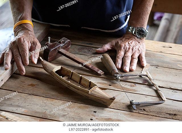 Craftsmans hands with a minature traditional Thai sampan made from teak wood, Bangkok Thailand