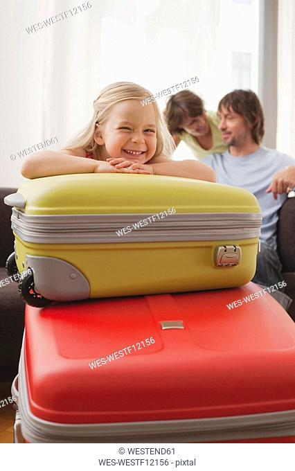 Germany, Leipzig, Girl 4-5 resting chin on suitcase, parents in background, smiling, portrait