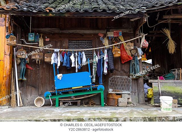 Matang, a Gejia Village in Guizhou, China. Bird Cages, Clothes, Miscellaneous Tools Hanging near Entrance to a Private Home