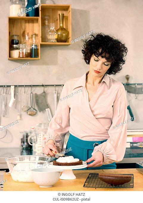 Woman spreading fresh cream on chocolate cake