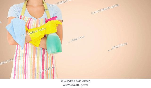 Female cleaner standing with napkin and spray bottle against beige background