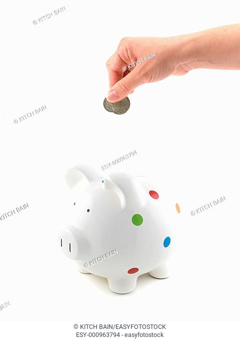 A female hand with coin and a piggy bank isolated against a white background