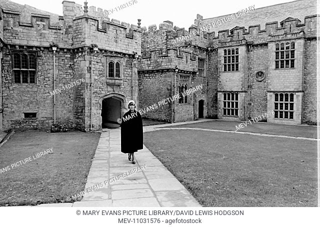 Nurse crossing the courtyard of Atlantic College (United World College of the Atlantic), St Donat's Castle, Llantwit Major, Glamorgan, South Wales