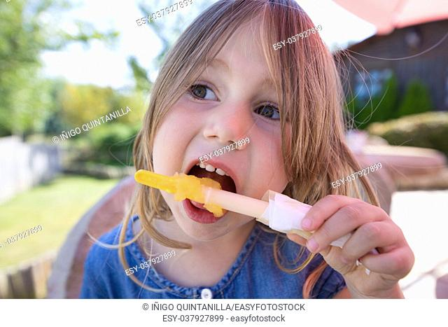 portrait close up of face of four years old blonde girl eating orange or yellow ice lolly or popsicle