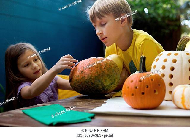 Boy and sister preparing pumpkins on garden table