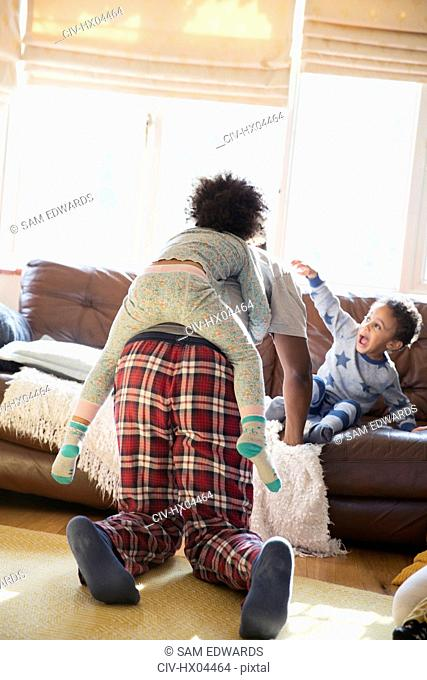Father and kids in pajamas playing in living room