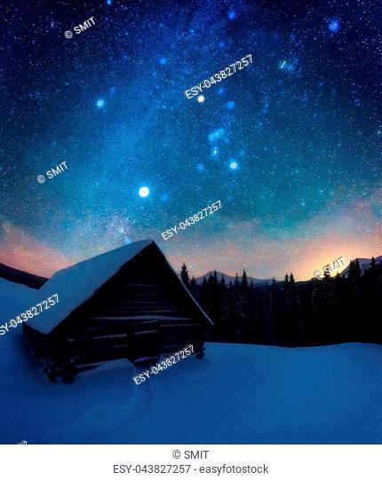 Fantastic night landscape glowing by milky way. Dramatic wintry scene with snowy house. Carpathian mountains, Ukraine, Europe