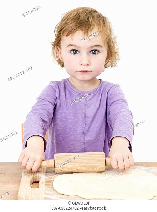 child making fresh pizza beginning with rolling out the dough