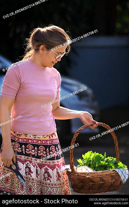 Woman holding a basket of vegetable from her organic homegrown garden