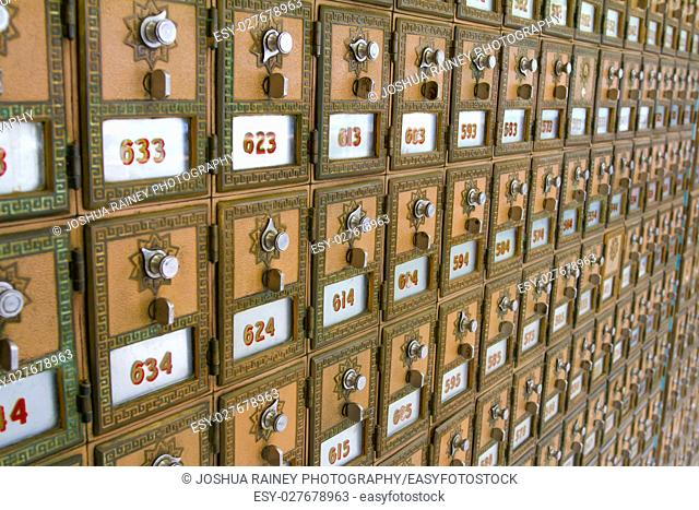 This photo shows the many po boxes at the post office. The mail boxes are lined up in rows and columns for organization