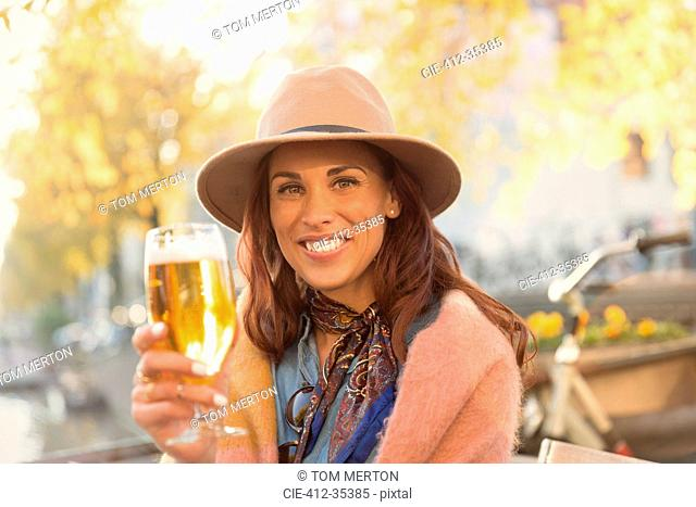 Portrait smiling young woman toasting beer glass at autumn sidewalk cafe