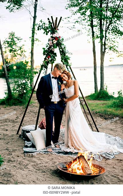 Bride and groom standing by lakeside campfire, Lake Ontario, Toronto, Canada