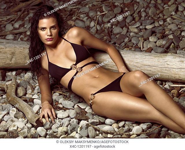 Beautiful young woman in black bikini posing on a pebbled beach  High fashion photo