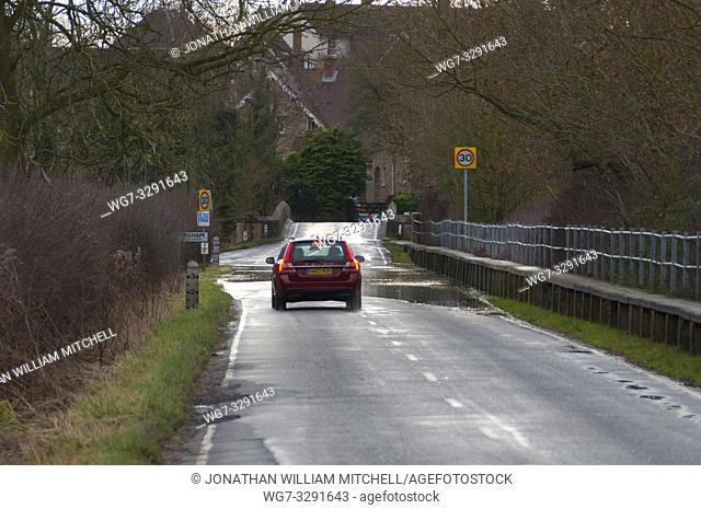 FELMERSHAM, ENGLAND, UK - Jan 5, 2014: A driver slows their Volvo car before floodwaters at the village of Felmersham, Bedfordshire, England