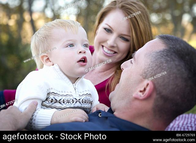 Cute child boy looks up to the sky as young parents smile