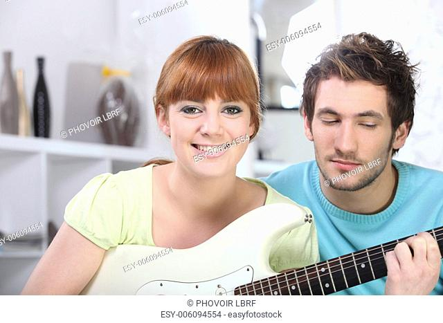 red-haired girl playing guitar