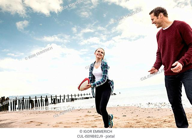 Father and daughter playing rugby on beach