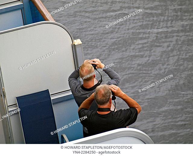 Two men with binoculars on a ships balcony