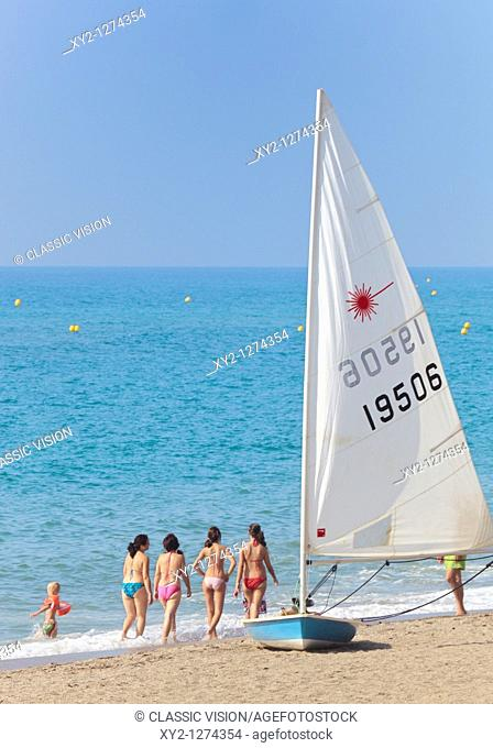 Costa del Sol beach scene shot at Cala de Mijas, Malaga Province, Spain with four girls walking by beached sailing boat and child in sea