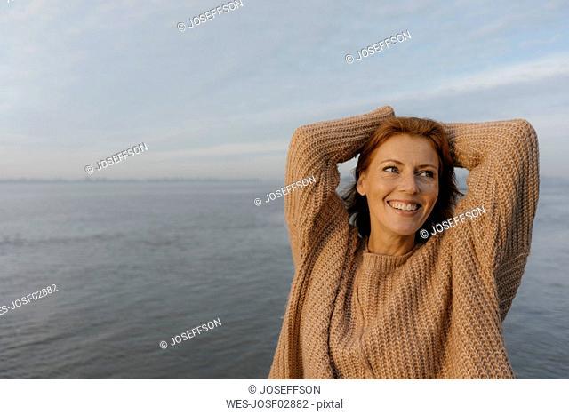 Germany, Hamburg, happy woman at the Elbe shore