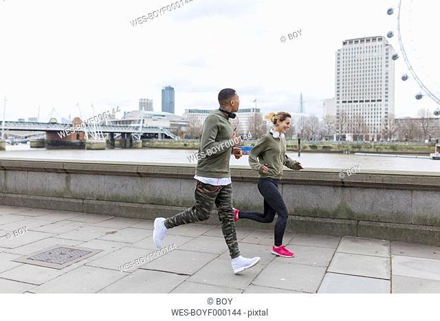 UK, London, man and woman running at riverwalk