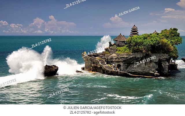 Wave crashing on Pura Tanah Lot, large rock with a Hindu temple in the ocean. Indonesia, Nusa Tenggara, Bali, Tabanan, Pura Tanah Lot