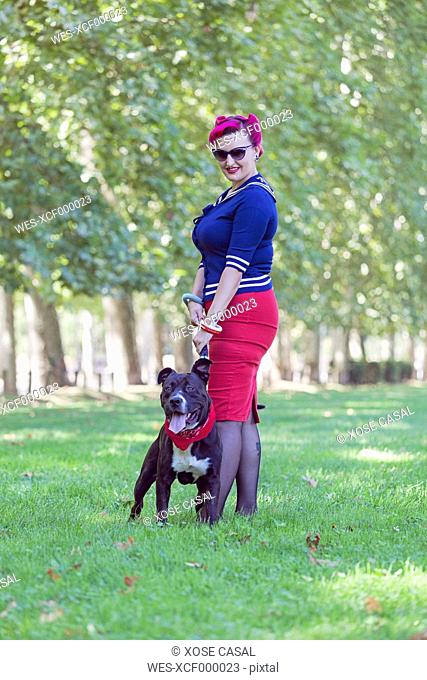 Portrait of woman with dyed hair standing on a meadow with her pit bull terrier
