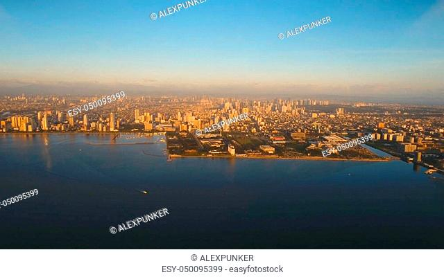 Aerial view skyline of Manila city, Makati. Fly over city with skyscrapers and buildings. Aerial skyline of Manila. Modern city by sea, highway, cars