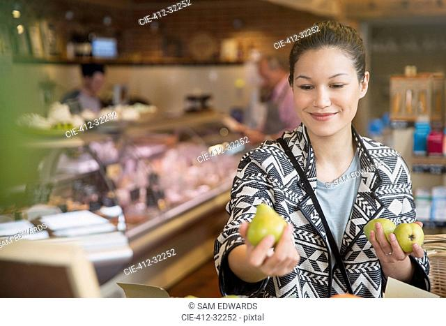 Smiling woman examining pears in market